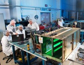 Grupa naukowców i inżynierów podczas testów urządzeń eksperymentu Saffire-II i Saffire-I (w tle). Żródło: NASA